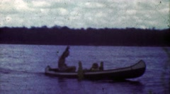 1953: Crafty man driving outboard motor rigged canoe across lake. Stock Footage