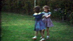 1953: Young girlfriends playing in backyard fall down tears ensue. Stock Footage