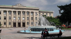 People passing by a fountain in front of Court Palace in Ruse Stock Footage