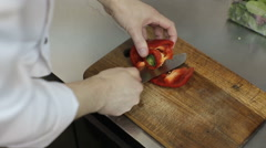 Close up of a chef slicing a red bell pepper on a wooden cutting board. Stock Footage