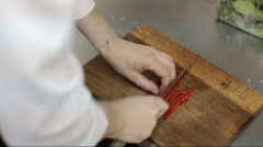 Close up of a chef slicing a red bell pepper on a wooden cutting board. - stock footage