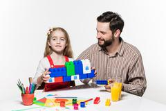 Father and daughter playing educational games together - stock photo
