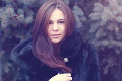 Beautiful brown-eyed brunette girl  winter  black coat posing  background trees - stock photo
