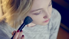 Young pretty blond girl doing makeup - stock footage