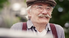 Old happy man sitting in nature Stock Footage