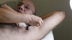 Shaving man's underarm before laser hair removal Stock Footage