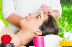 Closeup womans face receiving facial hair waxing treatment, hand using wooden - stock photo