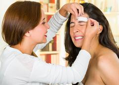 Professional eyebrow hair removal performed on client with painful facial Stock Photos