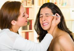 Woman performing eyebrow hair removal using tweezers on clients face Stock Photos