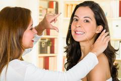 Cosmetologist performing facial hair removal using threading technique on - stock photo