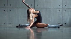 Young sexy blonde girl sits on a splits in studio Stock Footage