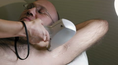 Man gets laser hair removal treatment underarm Stock Footage