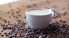 Coffee cup and beans on wooden table Stock Footage