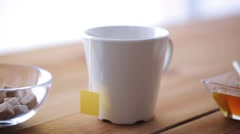 Tea bag and hot water pouring from kettle to cup Stock Footage