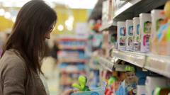 Young woman chooses baby toys in the supermarket Stock Footage