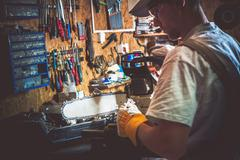 Gasoline Wood Cutter Chain Replacing in a Garage. Men Preparing Tools For Woo - stock photo