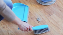 Woman with dustpan and brush sweeping floor Stock Footage