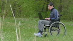 Disabled thinks problems man wheelchair with laptop in wheelchair working on Stock Footage