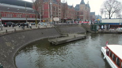 Amsterdam, The Netherlands. Tourist Boat On A Canal. Train Station Stock Footage