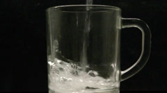 Water is poured in a glass tankard on the black background Stock Footage