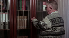 Retired older man with glasses takes a book from the bookcase and opened it Stock Footage