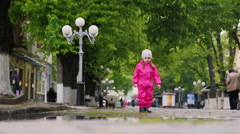 Girl in overalls and rubber boots running through puddles Stock Footage