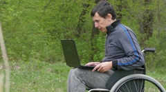 Man disabled video chat conversation wheelchair with a laptop in working on Stock Footage
