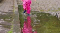 Children's feet in boots running through a puddle, reflection in water - stock footage