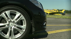 Portuguese aerodrome with an yellow airplane parked and a black mercedes Stock Footage