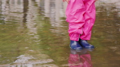 Fun spring - girl jumping in a puddle Stock Footage