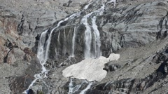 Waterfall in spring on the Aiguille des Glaciers in the Mont Blanc massif Stock Footage