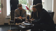 Men's Fashion - Three Young Men Looking at Fine Fabrics for Suits Stock Footage