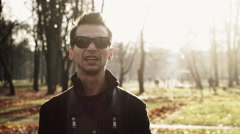 Stock Video Footage of Portrait of young man in sunglasses reads a rap in autumn park. Sunny