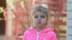 Girl five years old funny inflates cheeks - stock footage
