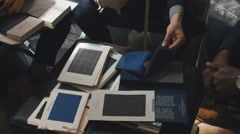 Overhead Close Up of Three Young Men Looking at Fine Fabrics for Suits - stock footage