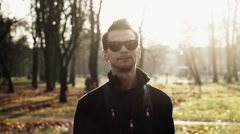 Stock Video Footage of Portrait of young man in sunglasses, jacket reads a rap in camera. Autumn park