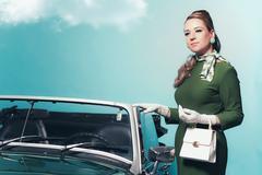 Retro 60s woman in green dress standing next convertible car. Stock Photos