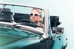 Vintage 60s fashion woman with shades driving sports car. Stock Photos