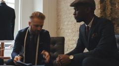 Young Caucasian Tailor Talking to Young Black Customer in Men's Fashion Shop Stock Footage