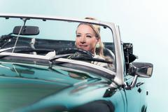 Smiling retro 1960s woman in sports car. - stock photo
