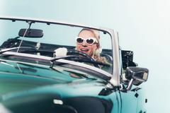 Smiling retro 1960s fashion woman with shades driving convertible. - stock photo