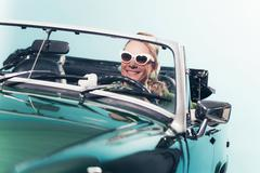 Smiling retro 1960s fashion woman with shades driving convertible. Kuvituskuvat
