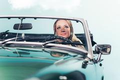 Classic 1960s fashion woman with headscarf driving sports car. - stock photo