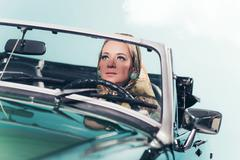 Classic 1960s fashion woman with headscarf driving sports car. Kuvituskuvat