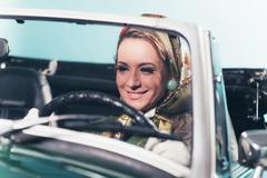 Smiling retro 1960s fashion woman with headscarf driving sports car. Kuvituskuvat