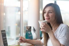 Young woman gazing out through cafe window Stock Photos
