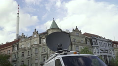 A news TV van with a satellite with a TV tower in the background in Prague. Stock Footage