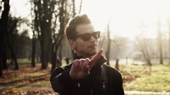 Stock Video Footage of Portrait of young man in sunglasses, sway reads a rap, gesture in camera. Autumn