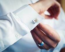 Groom buttons on his shirt cuffs Stock Photos