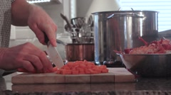 Chopping Carrots on cutting board in preparation for a lobster bisque - stock footage